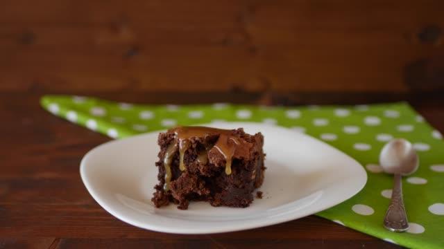droppar saltad karamell rinner ner en fyrkantig bit choklad brownie på en tallrik. - brownie bildbanksvideor och videomaterial från bakom kulisserna