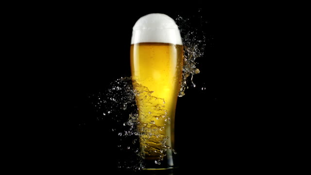 Drops of water crashing on a glass full of beer. Freshness metaphor Refreshing collision. Drops of water crashes on a glass full of beer. super Slow motion. Shot with Phantom. glass material stock videos & royalty-free footage