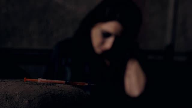 drogenmissbrauch. defokussierte junge frau nach einnahme der heroindosis - suchtkranker stock-videos und b-roll-filmmaterial