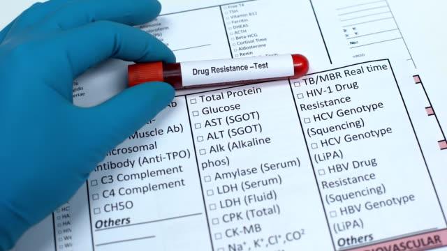 läkemedels resistens, läkare kontrol lera namn i lab blank, visar blod prov i röret - resistance bacteria bildbanksvideor och videomaterial från bakom kulisserna
