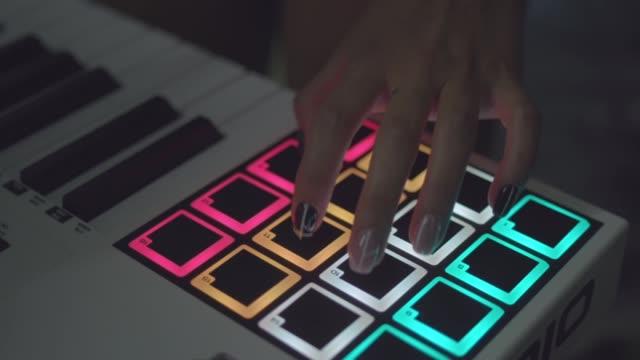 ライブセットを演奏するナイトクラブのドラムマシン。株式。指は、デジタルビートメーカークローズアップ上のドラムパッドをタップします。DJは、ドラムマシンを演奏するクラブで設定� ビデオ