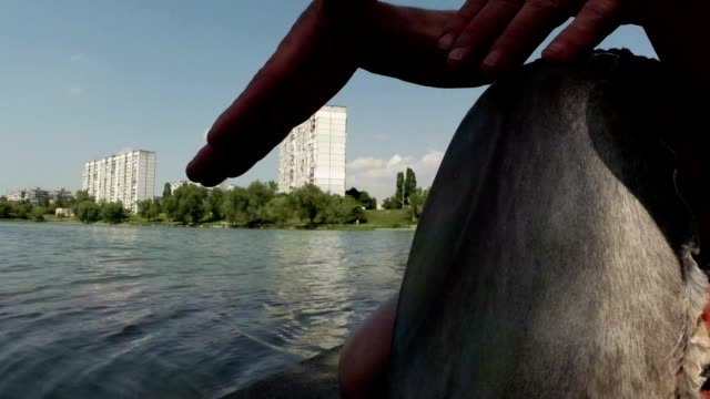 Drummer hands playing on a makeshift drum on a background of lake and building video