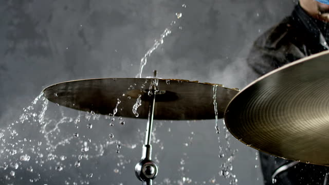 Drummer hitting on wet drum cymbal, and the water splashing from cymbal in slow motion 200 fps. Shot on RED HELIUM Cinema Camera. Drummer hitting on wet drum cymbal, and the water splashing from cymbal in slow motion 200 fps. Shot on RED HELIUM Cinema Camera. rock music stock videos & royalty-free footage