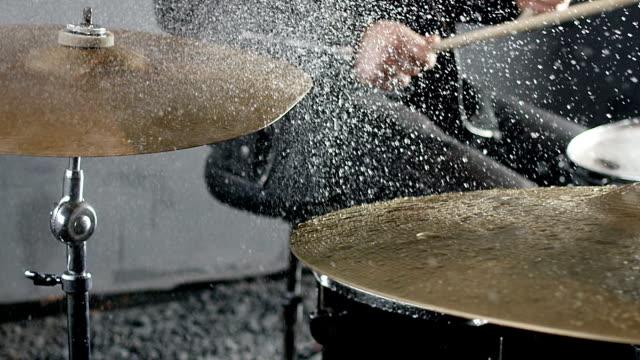 trummisen slår på våta trumma cymbal, och stänk från cymbal i slow motion 200 fps. skott på röda helium film kamera. - trumset bildbanksvideor och videomaterial från bakom kulisserna