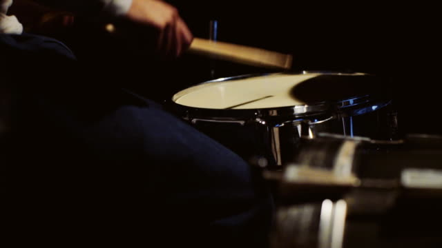 Drummer playing his drum kit on black background video