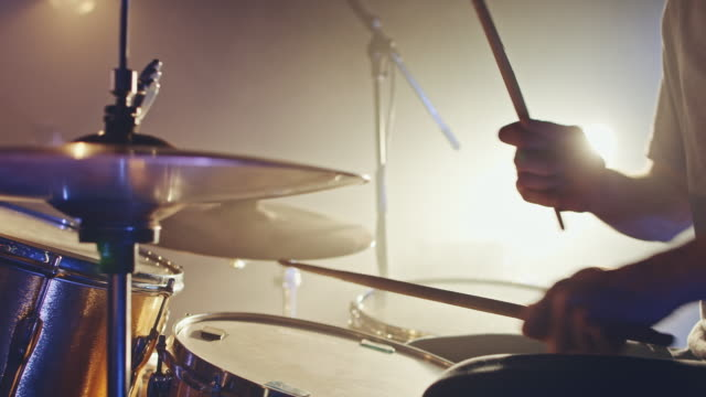 Drummer playing Drummer performing with his instrument on concert stage.   rock music stock videos & royalty-free footage