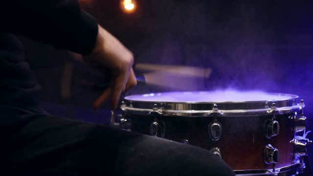Drummer playing with sticks on a snare drum with smoke with beautiful lighting.