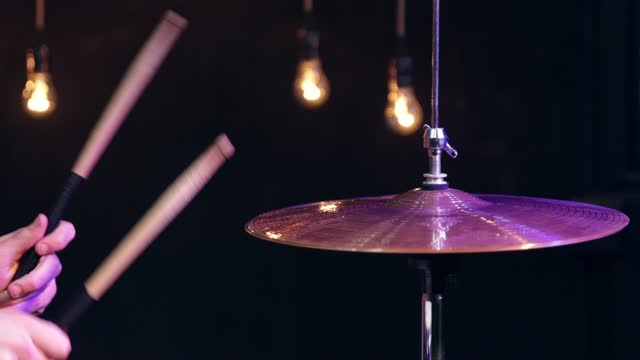 Drummer playing with sticks on hi hat close up in the dark.