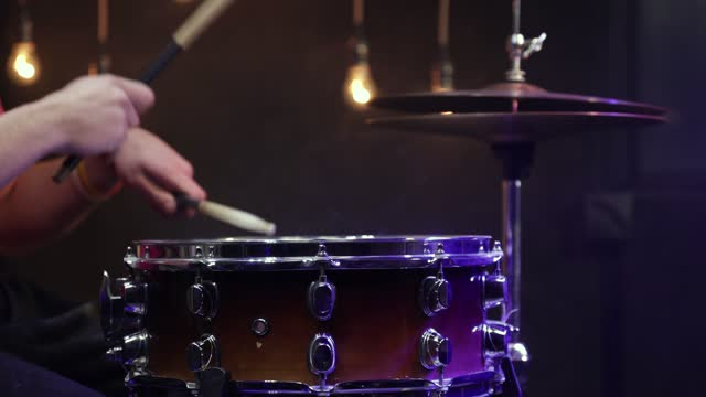 Drummer plays snare drum with sticks and dust hi-hat close up.