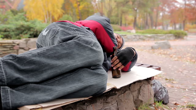 Drunk alcoholic sleeping on bench with empty bottle in hand, insolvent person