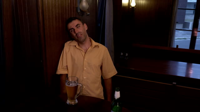 Drunk guy sitting a table in a pub cannot hold his glass with beer video