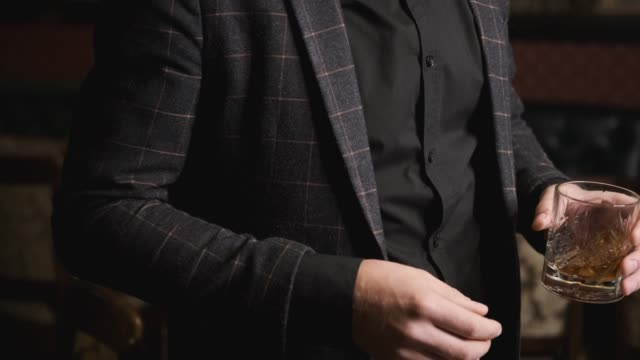 drunk man in a suit holding and twirling a glass of whiskey,concept alcohol - brandy video stock e b–roll