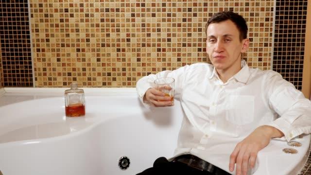 betrunkener mann in hose und hemd liegt im bad und trinkt alkohol - unterordnung stock-videos und b-roll-filmmaterial