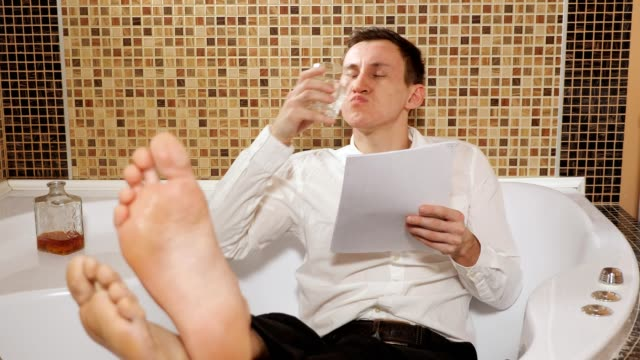 betrunkener mann in hose und hemd liegt in der badewanne und studiert dokumente, trinkt alkohol - unterordnung stock-videos und b-roll-filmmaterial