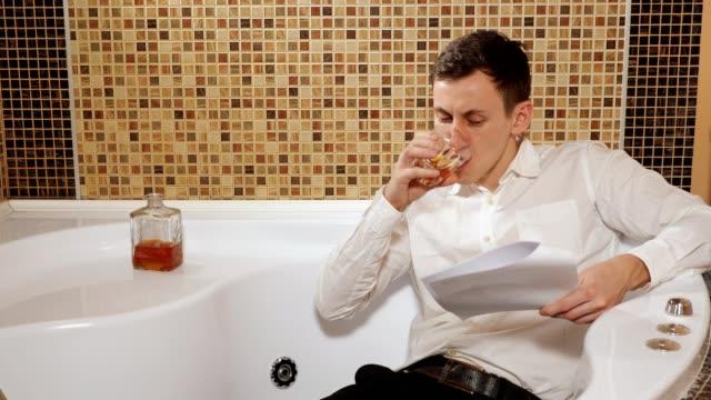 betrunkener mann in hose und hemd liegt in der badewanne und studiert dokumente - unterordnung stock-videos und b-roll-filmmaterial