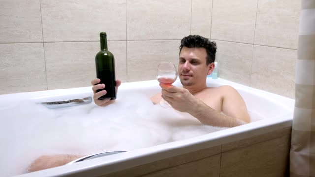 Drunk man lies in bath and spill wine on his face. video