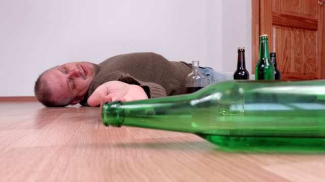 Drunk man sleep with bottle of hand video