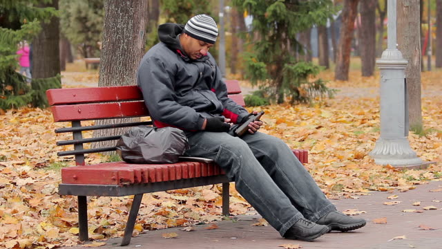 Drunk man sleeping on bench in park with bottle in hand, alcohol use disorder