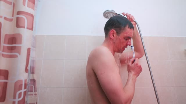 A drunk man standing in the shower sings a song on a toothbrush.