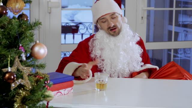 醉聖誕老人喝威士卡坐在桌旁 - 人造的 個影片檔及 b 捲影像
