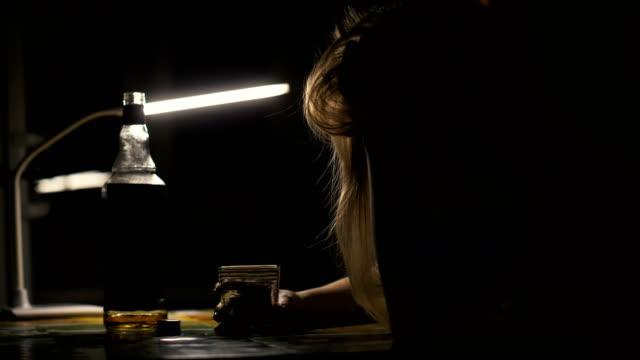 berusad kvinna sitter vid bord med glas whiskey och lägga huvudet på bordet - alcoholism bildbanksvideor och videomaterial från bakom kulisserna
