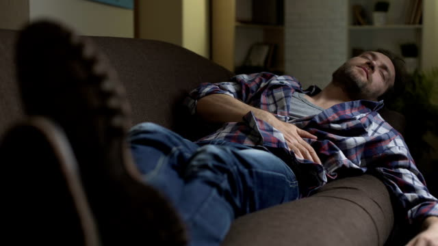 vídeos de stock e filmes b-roll de drunken man sleeping on couch, scratching belly in his sleep, after night out - sofá