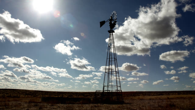 Dry grasslands windmill cloudscape sun lens flare time-lapse Yuma County prairie Colorado video
