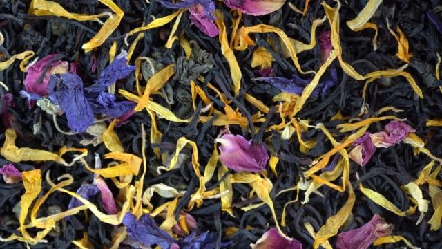 vidéos et rushes de thé d'herbes sèches avec des pétales de fruits et de fleur comme fond, vue supérieure, tourne - thé boisson chaude