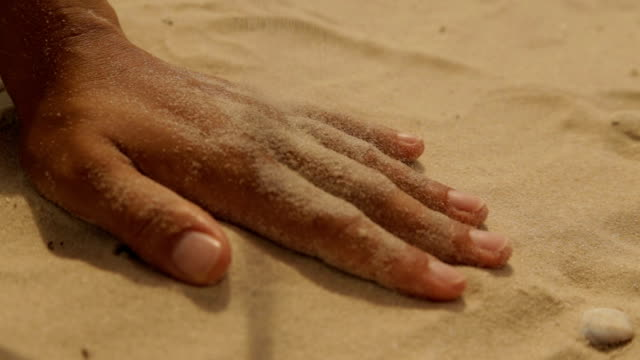 Dry sea sand on a woman's hand A girl on the beach pours sand on her hand handful stock videos & royalty-free footage