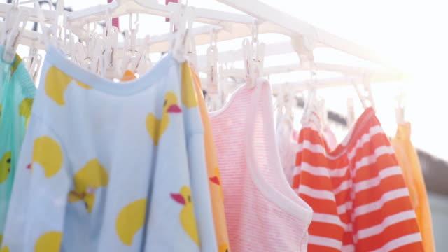 suszenie dziecka kolorowe ubrania wiszące na klipsie na zewnątrz. - pranie filmów i materiałów b-roll