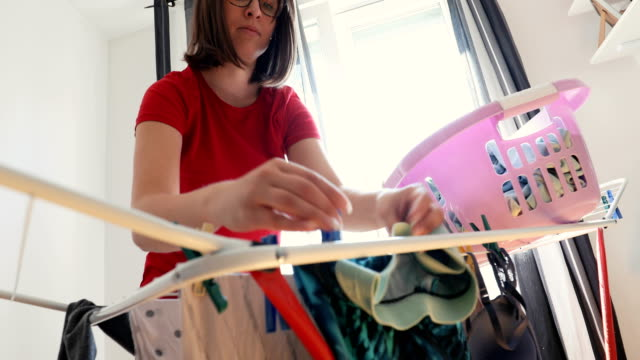Drying clothes naturally A woman is putting clothes on a drying rack. laundry basket stock videos & royalty-free footage