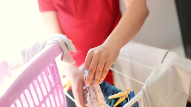Drying clothes naturally Closeup footage of an unrecognizable woman who is putting her clothes on a drying rack. She is using clothes peg to attach it. laundry basket stock videos & royalty-free footage