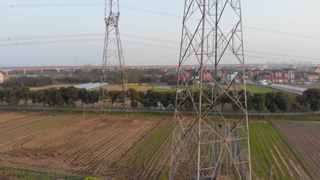 Dual power towers in farmland drone shot rising up.