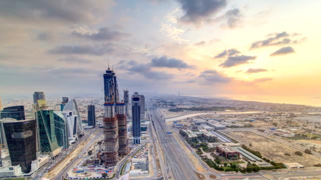 dubai business bay torn med sunset timelapse. takterrass med utsikt över några skyskrapor och nya torn under konstruktion - tävlingsdistans bildbanksvideor och videomaterial från bakom kulisserna