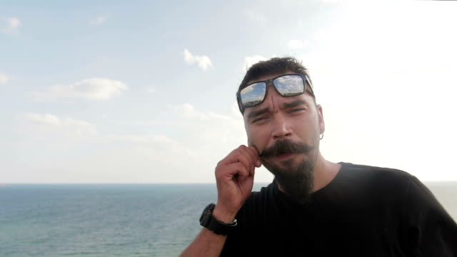 dude beatnik with mustache, and glasses on the background of the sea. movember - baffo peluria del viso video stock e b–roll