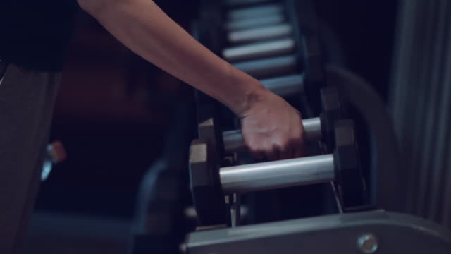 Dumbbells sports and fitness weight training equipment Unrecognizable person taking free weights at the gym. Thailand. rack stock videos & royalty-free footage