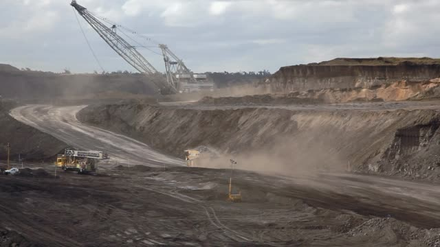 Dump truck and dragline at open-pit coal mine A dump truck loaded with coal kicks up a dust cloud as it drives toward a the surface at an open-pit coal mine with a giant dragline in the background dump truck stock videos & royalty-free footage