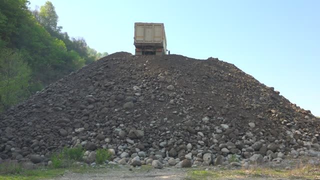 Dump truck dumping unloading sand and gravel mix