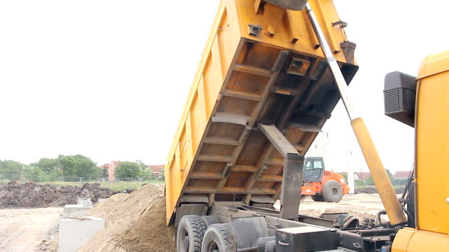 Dump truck is unloading soil Dumper truck is unloading soil or sand at construction site. civil engineering stock videos & royalty-free footage