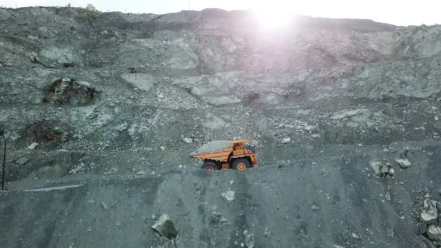 Dump truck loaded with chalk moving on a quarry road. Quarry and mining equipment video