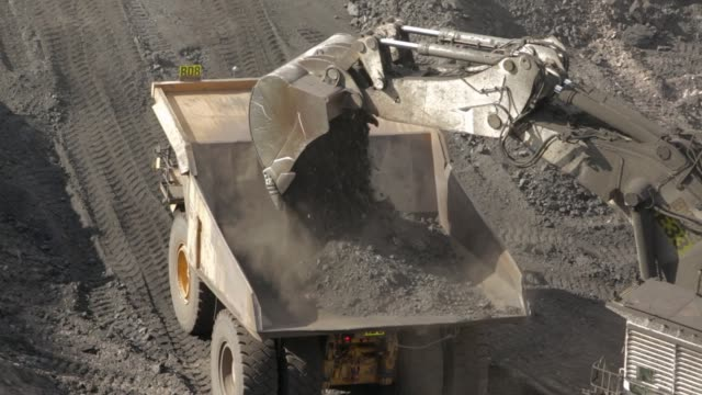 Dump truck loaded with coal A dump truck is loaded with dirt at a coal mine. construction machinery stock videos & royalty-free footage