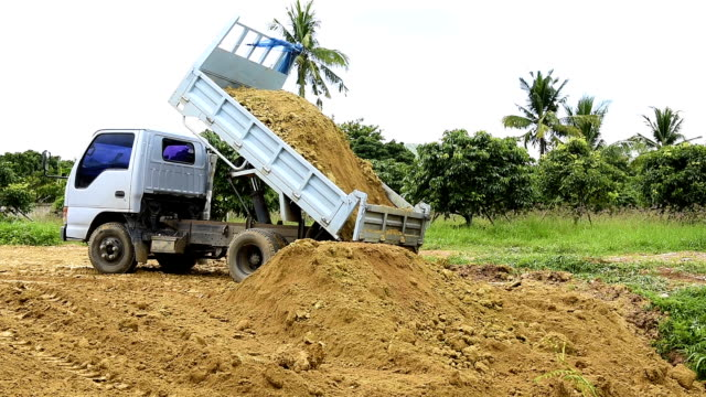 Dump truck unloading soil at construction site Dump truck unloading soil at construction site dump truck stock videos & royalty-free footage