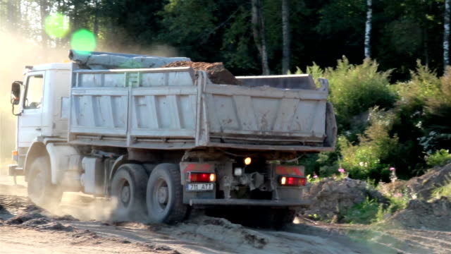 A dump white truck ready to unload and running backwards video