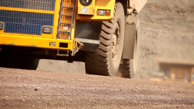 A dumper rides along the road, Yellow dump truck is in the quarry, Industrial exterior