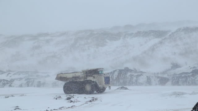 A dumper truck drives through an open-pit coal mine in winter A dumper truck drives through an open-pit coal mine in winter through a blizzard and snow construction equipment stock videos & royalty-free footage