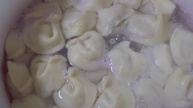 vídeos de stock e filmes b-roll de dumplings are boiled in a saucepan on a gas stove. cooking dumplings - ravioli