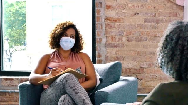 vidéos et rushes de pendant la pandémie covide-19, un conseiller et un patient portant des masques et des distanciations sociales pendant la séance de counseling - thérapie alternative