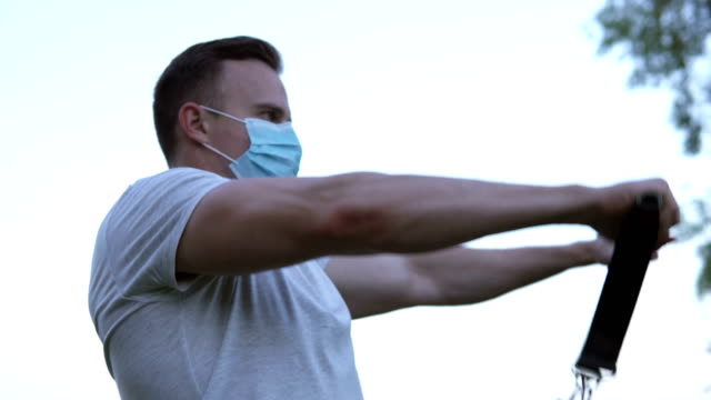 During the quarantine period, the athlete plays sports on the street in a mask. Athlete does exercises with an expander. video