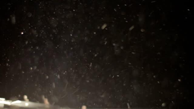 staubfliegen, die von einer suchscheinwerfer in der dunkelheit beleuchtet werden - sägemehl stock-videos und b-roll-filmmaterial