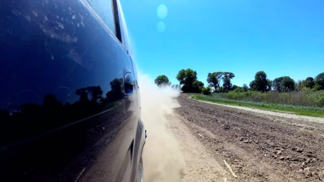 dust rising from automobile wheels automobile driving on rural gravel road. - ghiaia video stock e b–roll
